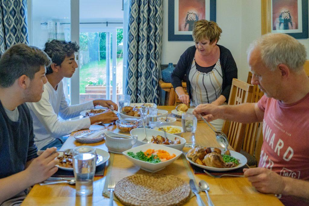 English host family with two international students enjoying a full English roast dinner